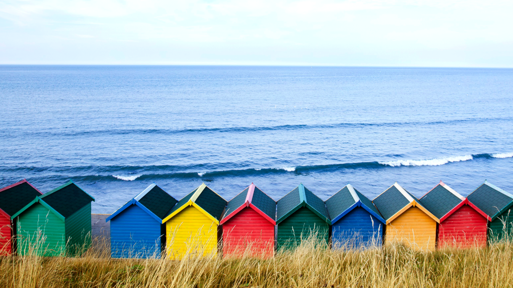 Colourful beach huts along the seafront, North Yorkshire, Whitby, England, UK