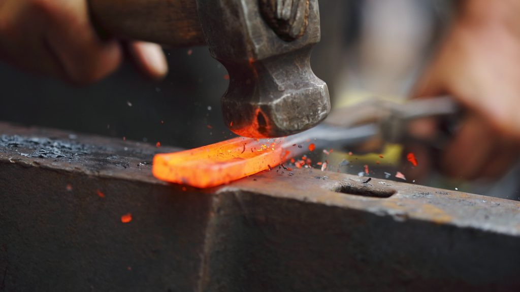 Detail shot of hammer forging hot iron at anvil, Slovakia