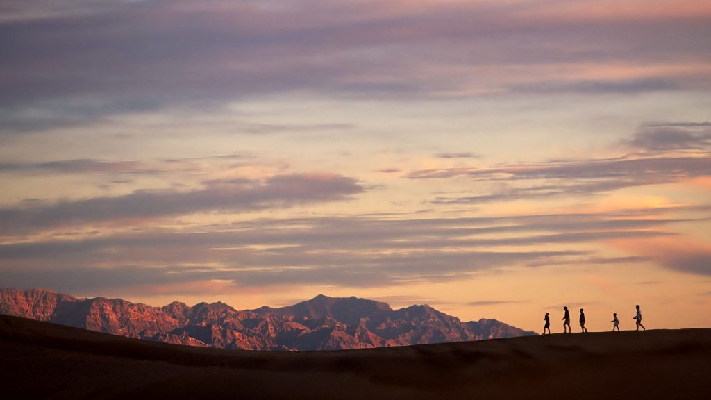Silhouette of family hiking at sunset, Death Valley, California, USA