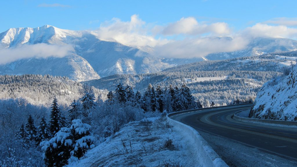 Empty road through snowy mountains in winter, Alberta, Canada