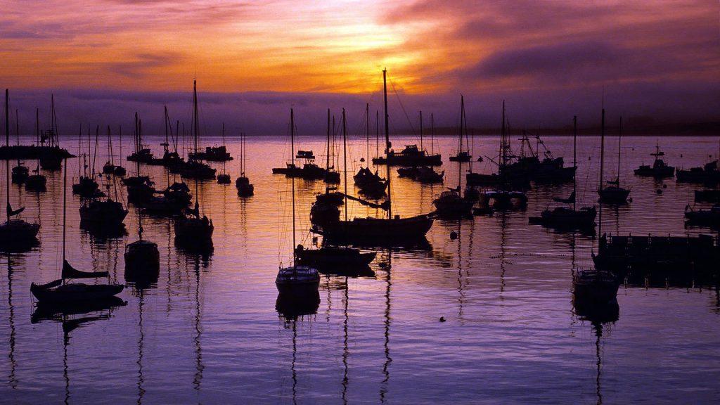 Sunrise over moored boats in Monterey Bay Harbor, California, USA