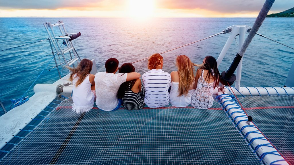 Friends relaxing on boat in ocean, Hawaii islands, USA