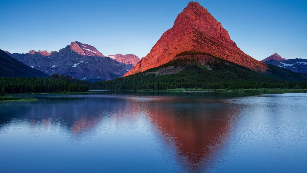 Mount Grinnell view over Swiftcurrent Lake at sunrise in Montana's Glacier National Park, USA