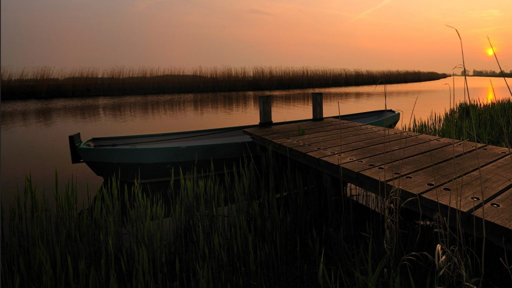 Beautiful sunset with a boat and small pier, Schermerhorn, Netherlands