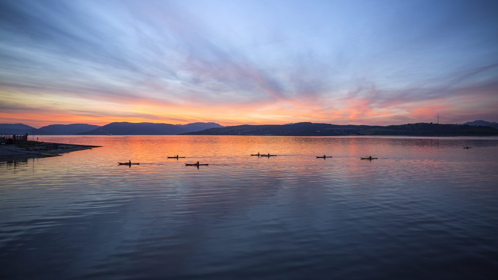 Kayakers on the coast at sunset, Firth of Clyde, Greenock, Scotland, UK
