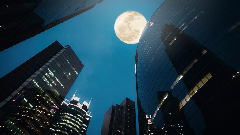 Full moon rises over commercial skyscrapers, Hong Kong, China