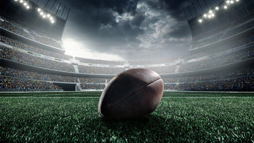 American football ball on stadium field