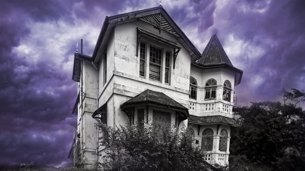 A derelict old mansion on top of a hill