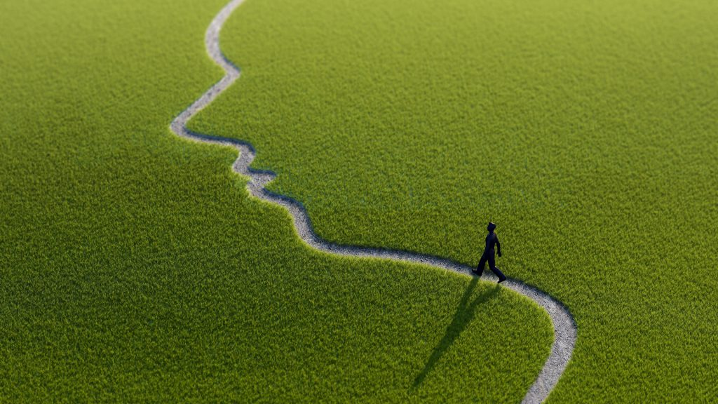 Lonely person walking along face-shaped path artwork