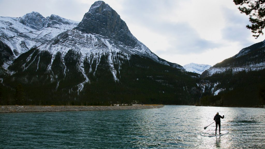 A woman enjoys a wintertime stand up paddleboard trip, Canada