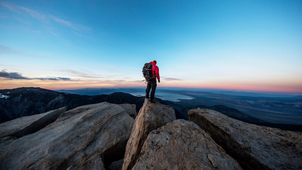 Climber on the summit of a peak watching sunset, Sierra Mountains, California, USA
