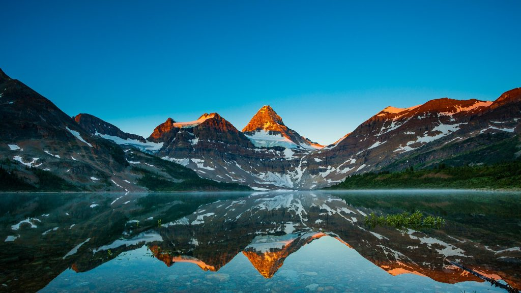 Reflection of mount Assiniboine in Magog lake at sunrise, Alberta, Canada