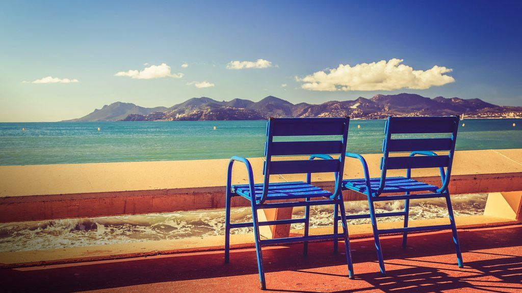 Blue chairs on the Croisette in Cannes at a sunny day, France