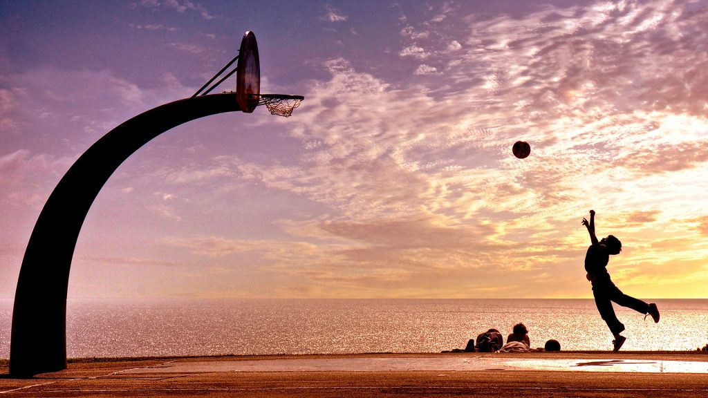 Boy throwing ball in basket at sunset by ocean, San Pedro, Los Angeles, California, USA
