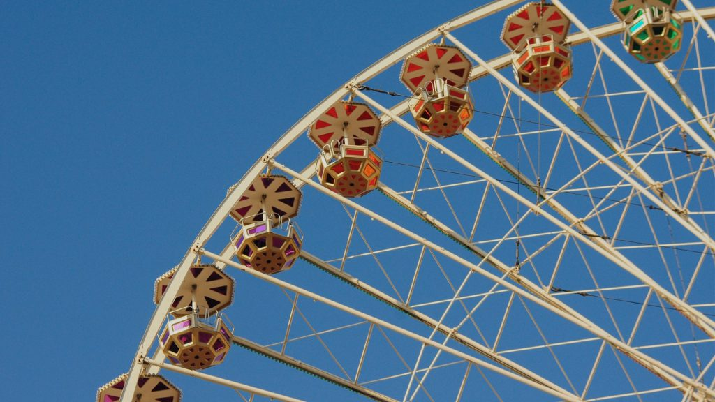 Vintage colorful ferris wheel against a sunny blue sky, retro fun at a summer fair or a carnival