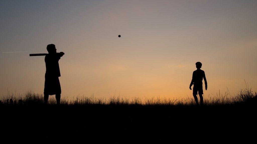 Silhouette of man and teenage boy playing baseball