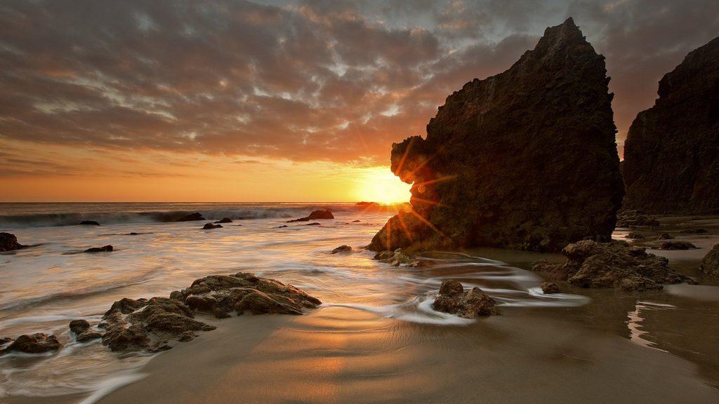 The last rays of the day shine at Malibu beach in California, USA