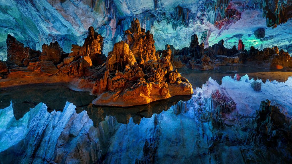 Reflections in still water inside the Reed Flute Cave, Guilin, China