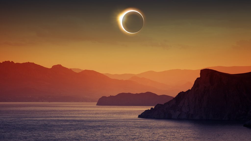Total solar eclipse, mountains and sea