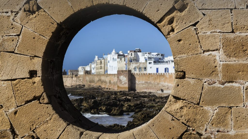 The fortified city of Essaouira view through hole in brick wall, Morocco