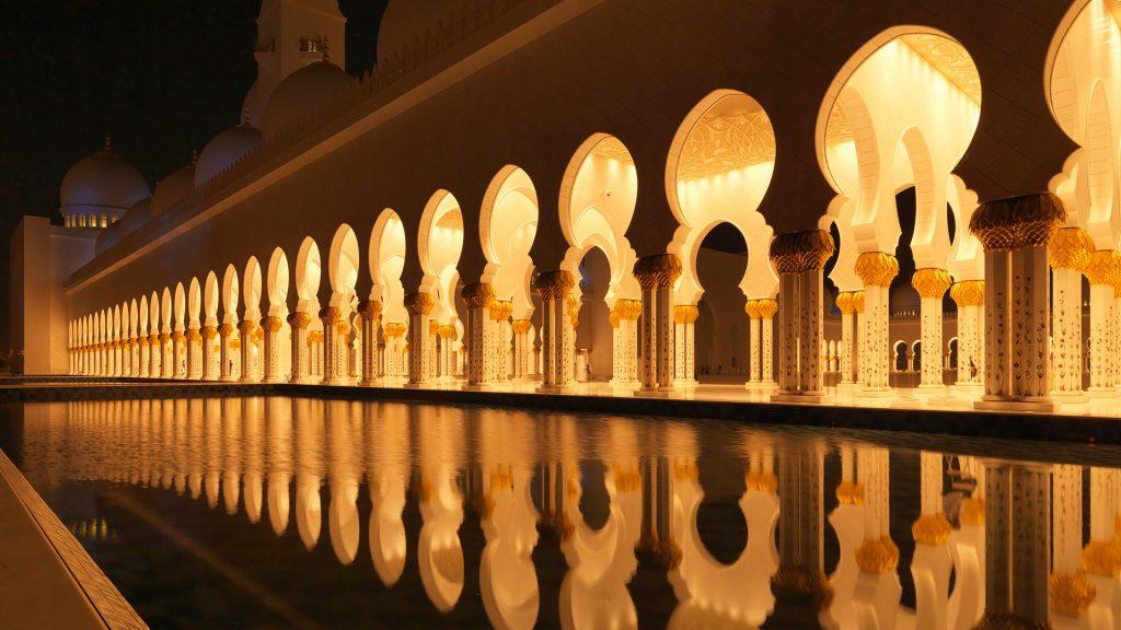 Illuminated colonnade reflecting in still pool, Abu Dhabi, UAE