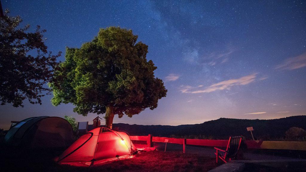 Red illuminated tent under the stars at night, Saxon Switzerland, Germany