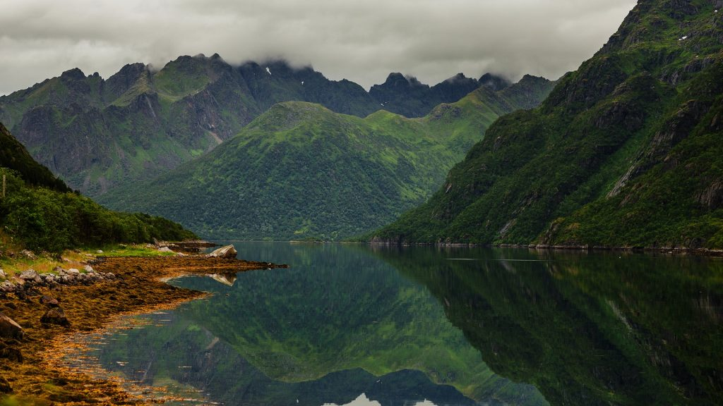 Rugged green mountains reflected in a lake in Norway