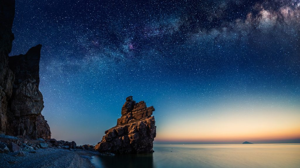 Starry night over rock formations by the Pacific Ocean, Dalian, Liaoning, China