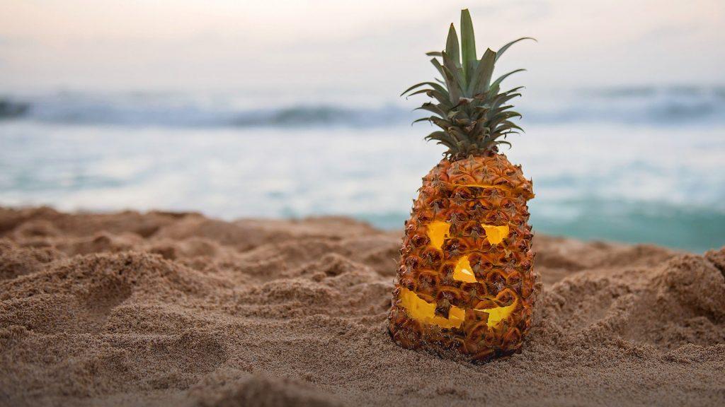 Pineapple carved like a jack-o'-lantern on beach at dusk, Hawaii, USA