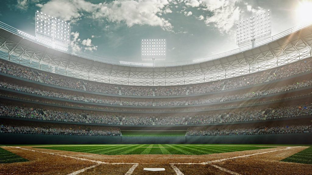 Outdoor baseball stadium full of spectators under a cloudy sky at midday