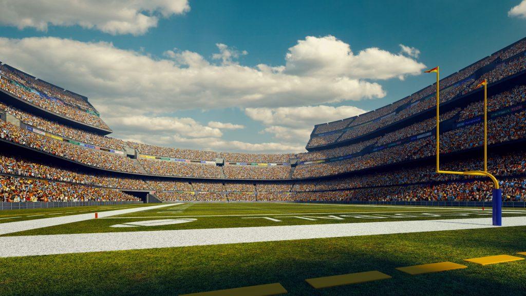 Sunny american football stadium full of spectators under blue sky