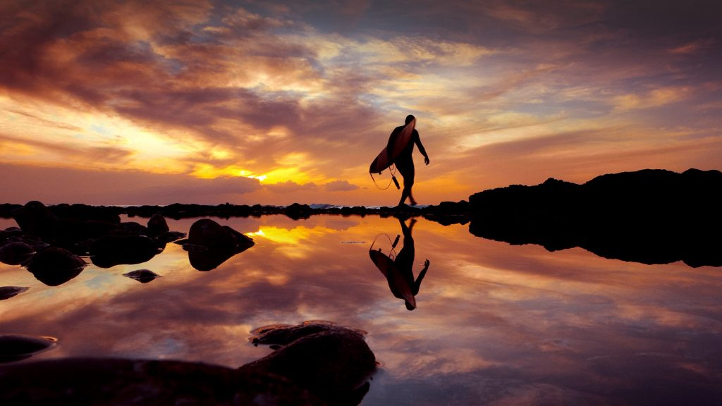 Surfer at sunset by the sea, Playa de las Américas, Tenerife, Canary Islands, Spain