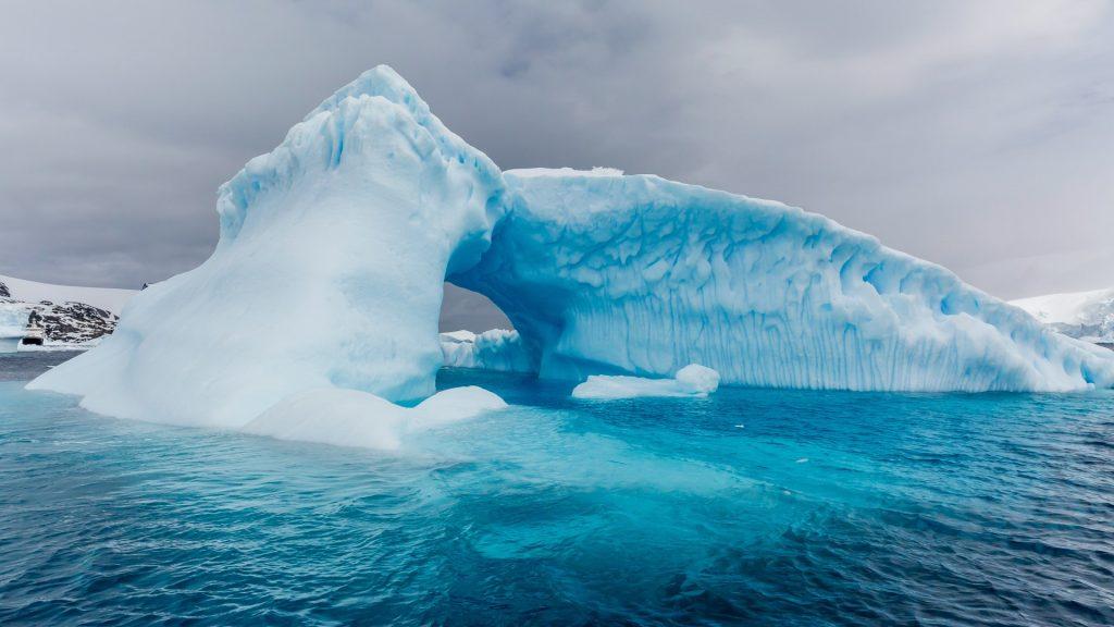 Archway formed in a glacial iceberg at Cierva Cove, Antarctica