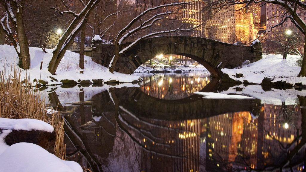 Gapstow Bridge in Central Park in Manhattan after a snow storm at dusk, New York City, USA