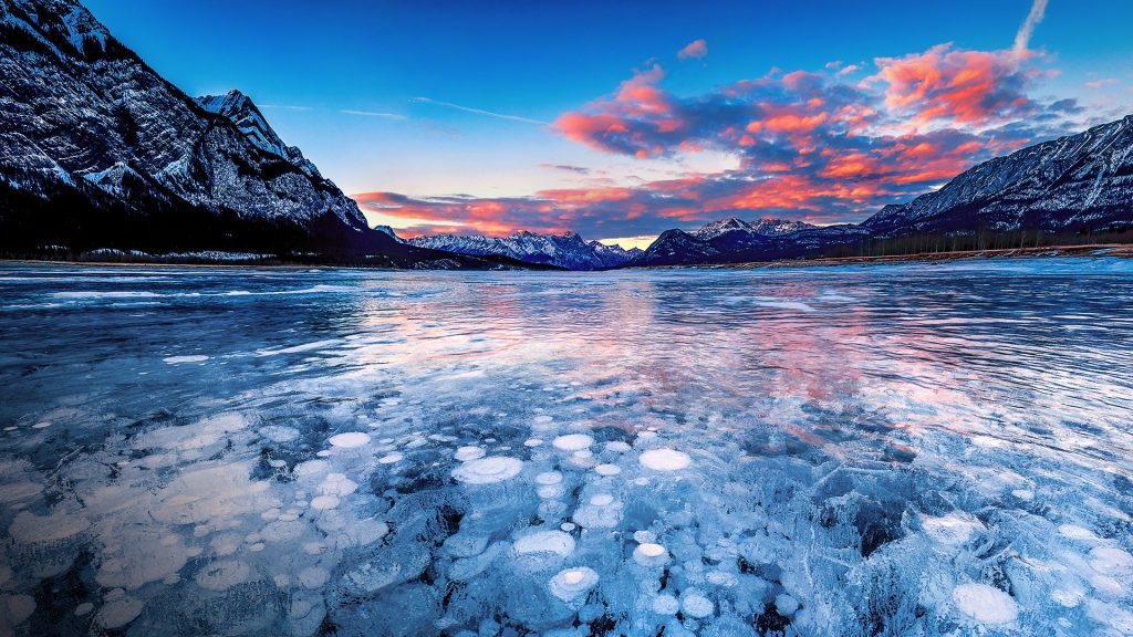 Stacks of methane bubbles under ice in Abraham Lake at sunset, Alberta, Canada