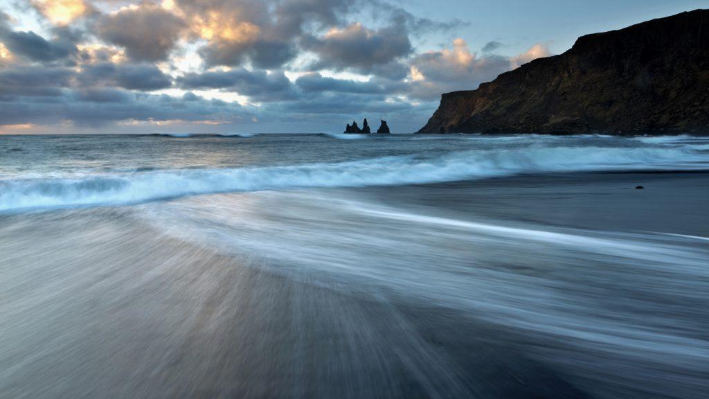 Sea stacks of Reynisdrangar at sunrise from the black volcanic sand beach at Vík í Mýrdal, South Iceland