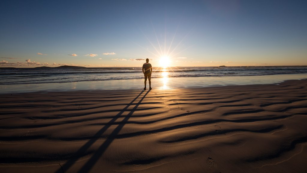 Man standing on beach looking at the sunset, Western Australia