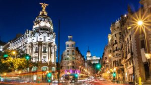 Rays of traffic lights on Gran via street, main shopping street in Madrid at night, Spain