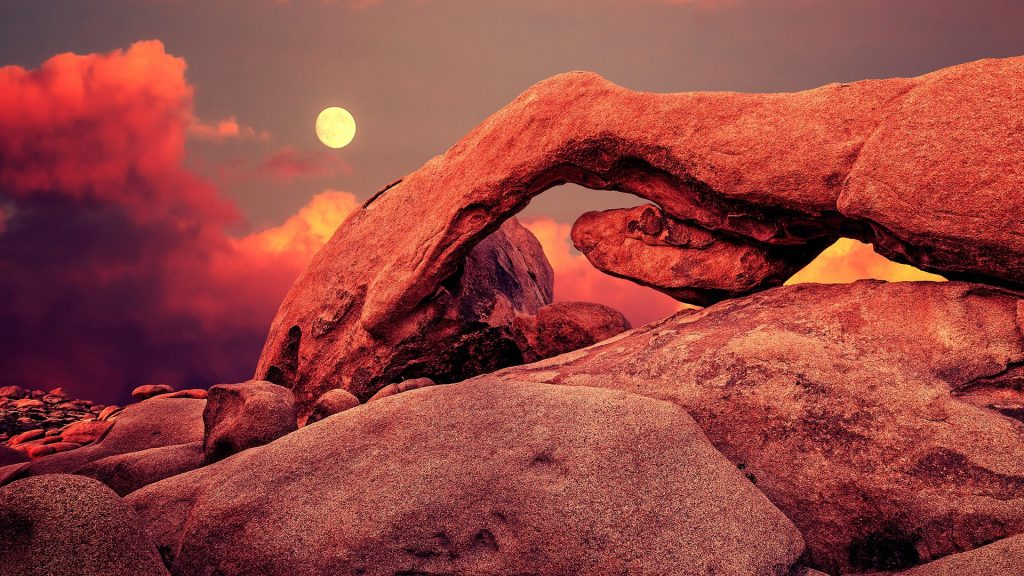 Purple sunset and rising moon over arch in Joshua Tree National Park, California, USA
