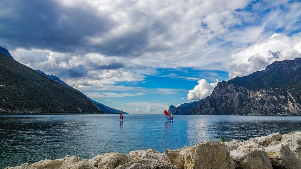 Surfers between mountains on Lake Garda, Italy