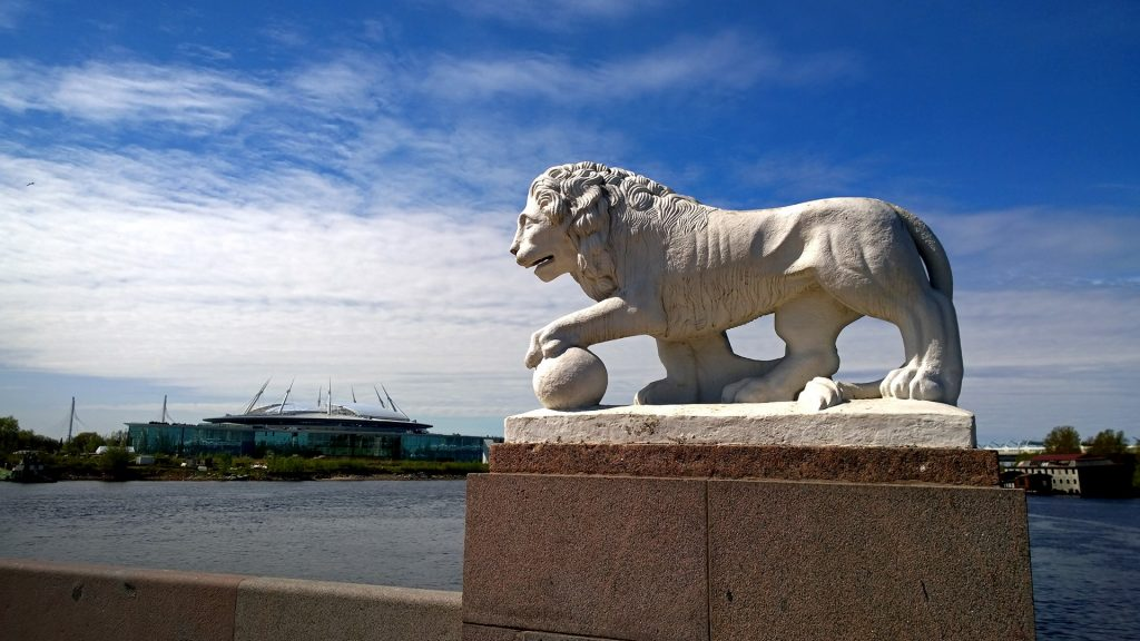 Lion sculpture on Elagin island with Saint Petersburg stadium in background, Russia