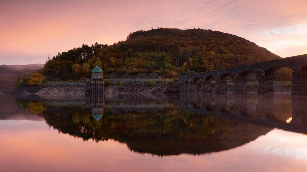 Autumn colours on still morning at Craig Goch Dam in the Elan Valley, Powis, Wales, UK