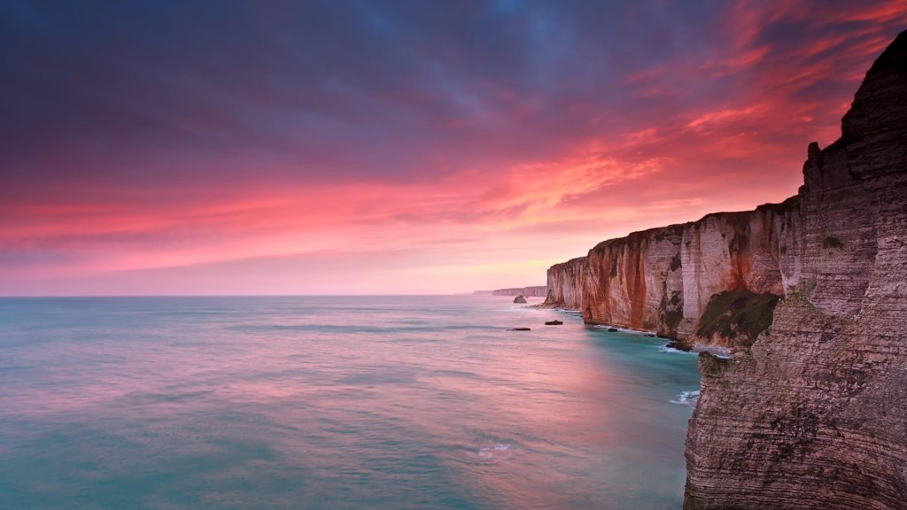 Dramatic fire sunrise over ocean and cliffs, Étretat, France