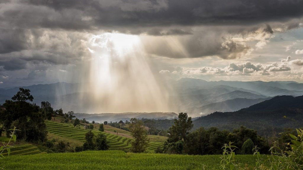 Storm clouds with rain and sunbeam over the mountain, Thailand