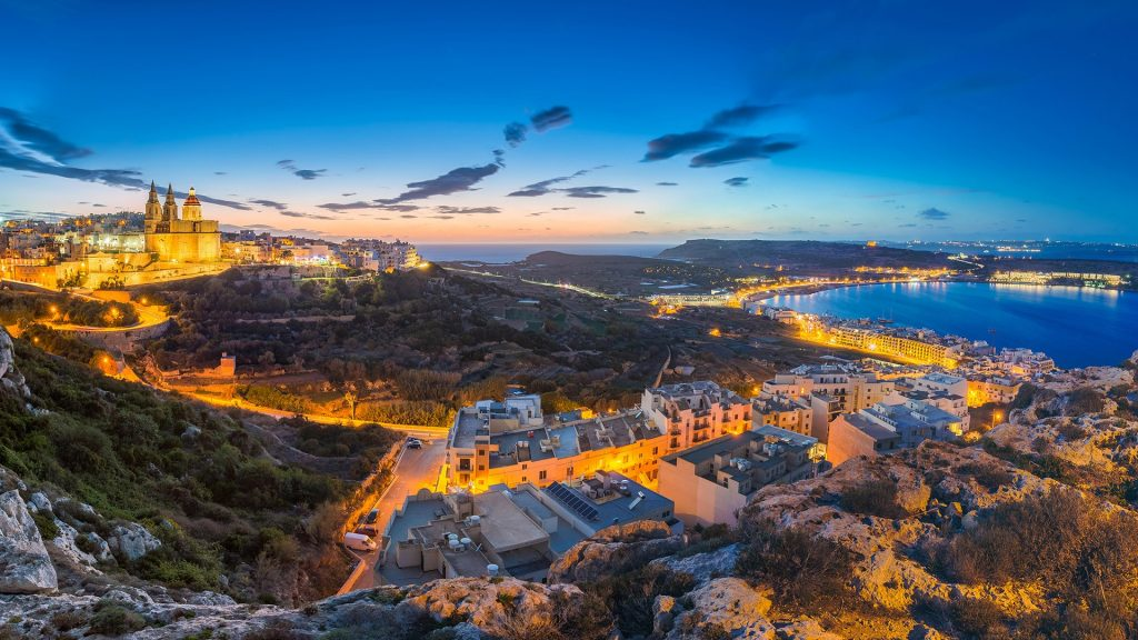 Skyline view of Mellieħa town after sunset with Parish Church and beach, Malta