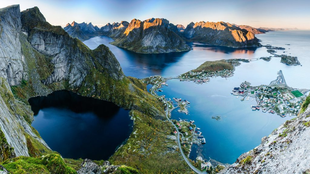 Sunset aerial view from Reinebringen ridge on mountains and village of Reine in Lofoten islands, Norway