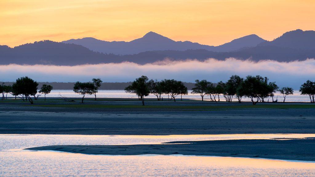 Sunset fog behind trees at Bangben Lake, Ranong, Thailand