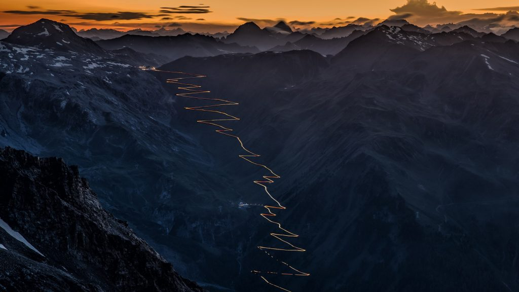 Mountain road Stelvio Pass curves at night with traffic lights, Italy