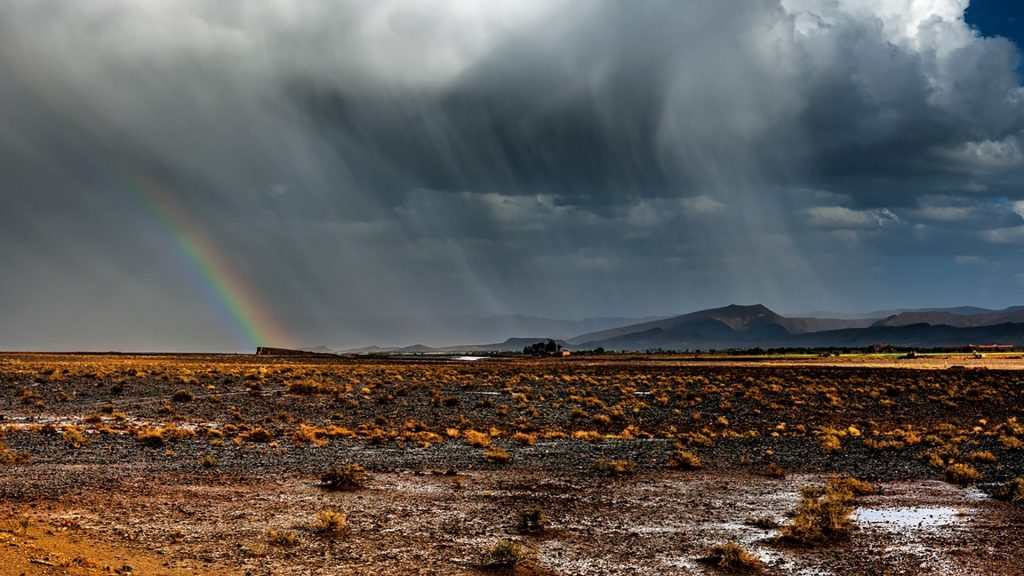 Thunderstorm with rainbow in desert, Morocco