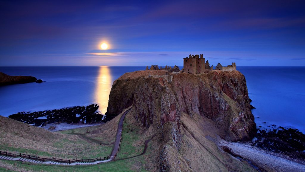 Full moon over calm sea and Dunnottar castle near Stonehaven, Aberdeenshire, Scotland, UK